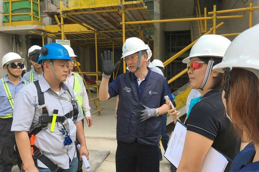 Minister of State for Manpower Sam Tan speaking to workers at a condominium construction site on Match 17, 2016.