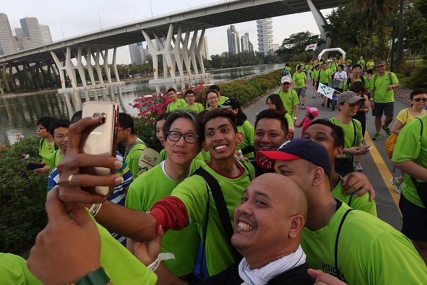 Minister for Manpower Mr Lim Swee Say takes a wefie with participants of the 3.5km walk at Gardens by the Bay East.