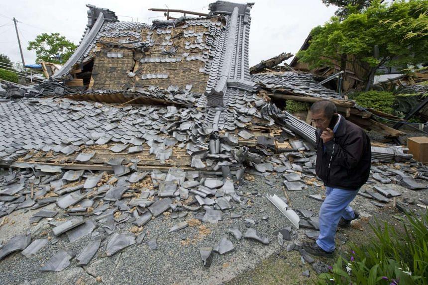 A man walks past a destroyed Buddhist temple in Mashiki, Kumamoto Prefecture, southwestern Japan on April 18, 2016.