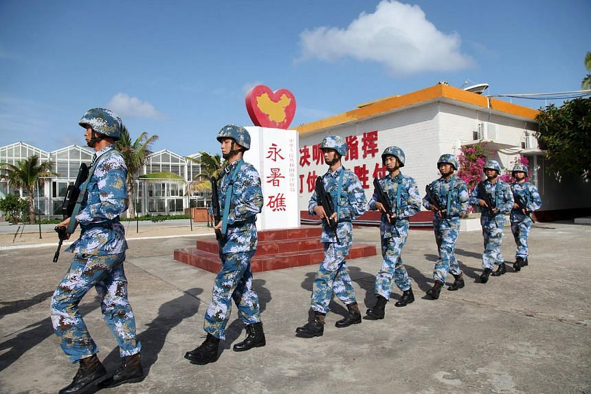 Soldiers of China's People's Liberation Army (PLA) Navy patrol at Fiery Cross Reef, in Nansha Islands on Feb 9, 2016.