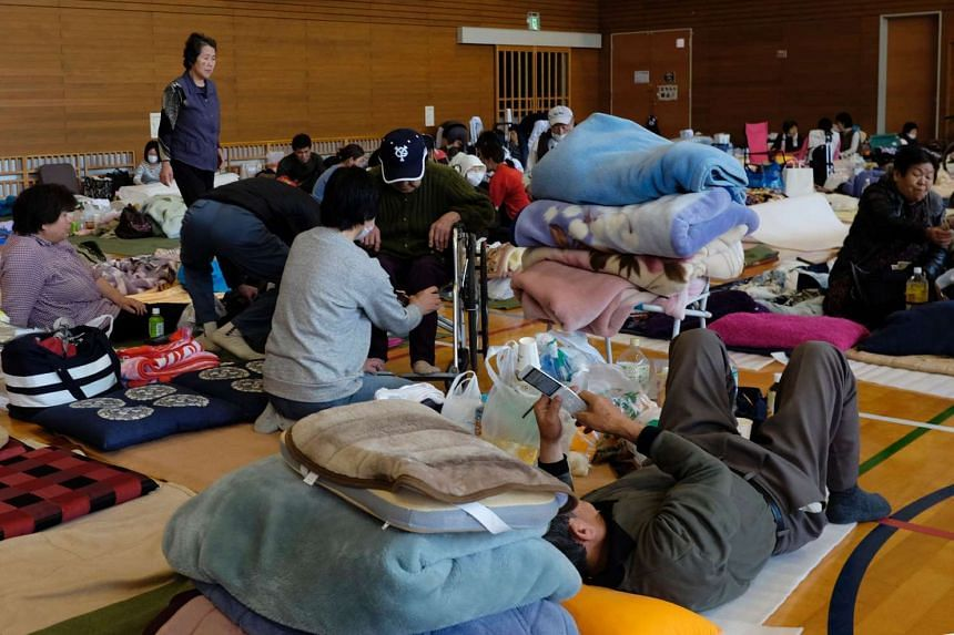 Japanese evacuees rest at an elementary school in the village of Nishihara, in Kumamoto prefecture, on April 17, 2016.