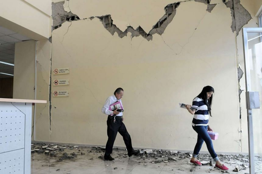 People walking in a damaged building in the city of Guayaquil, Ecuador on April 17, 2016, which was hit the day before by a 7.8-magnitude earthquake.