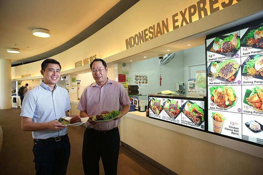 Mr Peh (far left) and Mr Ng with some of the healthier dishes available at their food stalls in NUS. Their stalls have joined HPB's Healthier Dining Programme, under which they receive help to come up with healthier meal options.