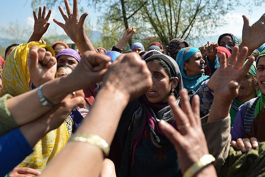 Kashmiri villagers shouting pro-freedom slogans during the funeral of a woman who was caught in crossfire during a gun battle between soldiers and militants. Locals have in recent months converged on the scene of gunfights between government forces a