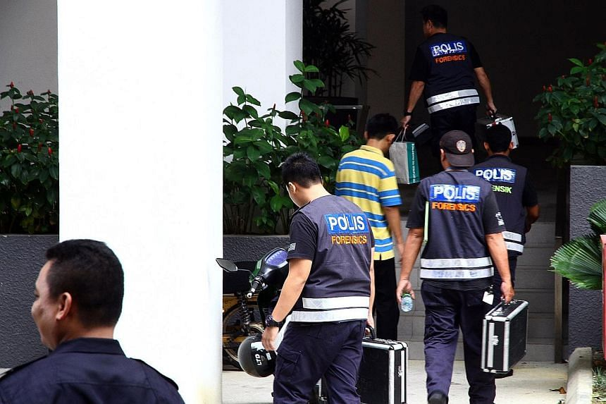 Police at the condominium block in Selangor where five homemade bombs were found yesterday following a raid.