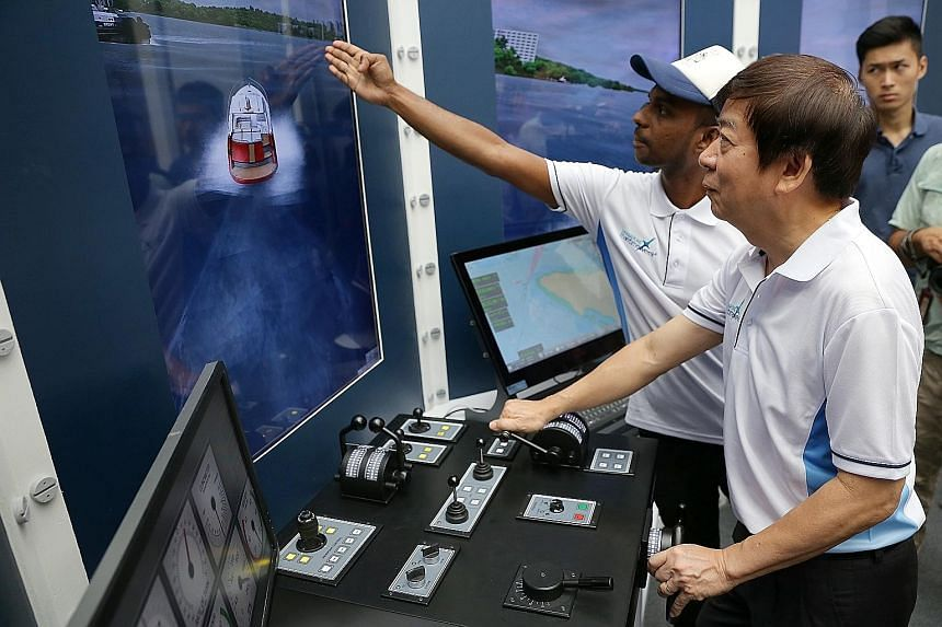 Mr Rajamohan Krishnan, 33, from the Singapore Maritime Academy, guiding Transport Minister Khaw on a ship simulator as the latter navigates a ship away from big vessels and berths it at the port successfully.