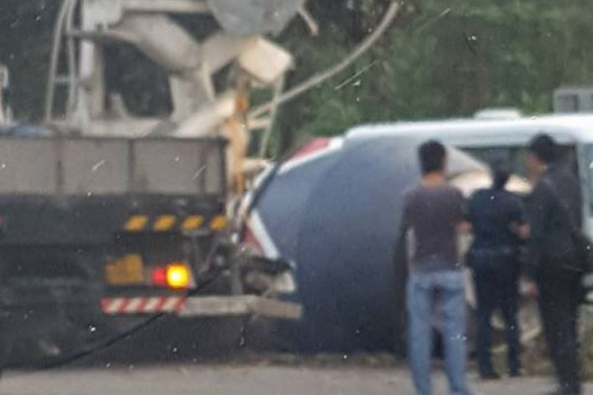 Police officers gathered around the overturned cement mixer.