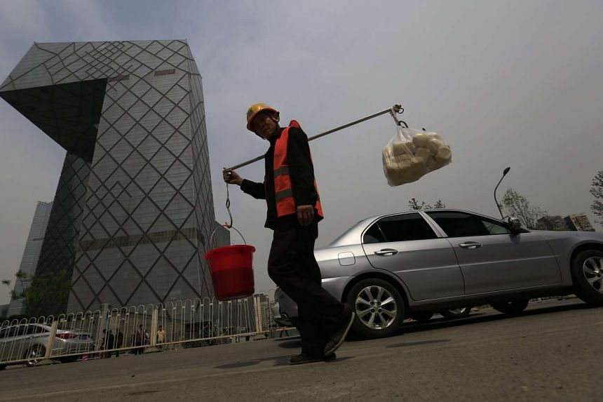 A Chinese construction worker carrying supplies with a pole, walking past the China Central Television (CCTV) Tower in Beijing, China, on April 15, 2016.