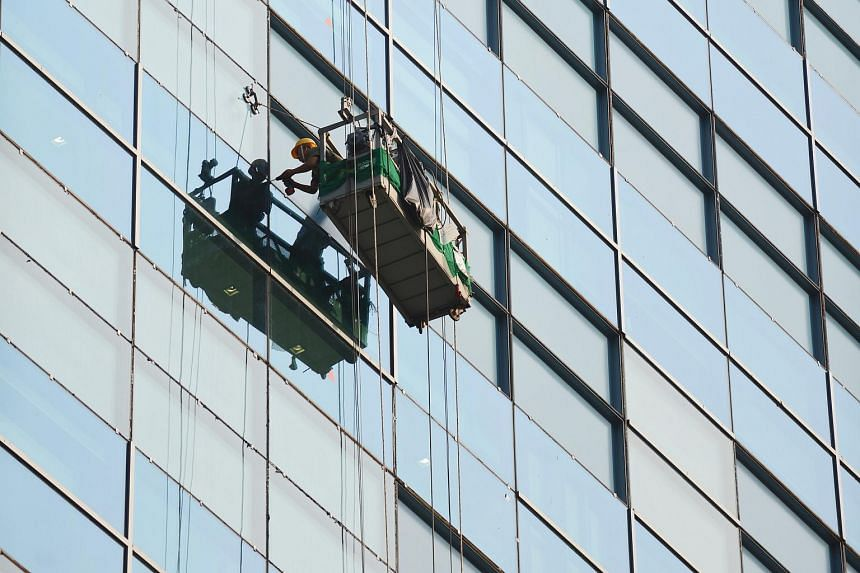Workers cleaning a facade of the JTC Building in Fusionopolis. iHub said FLEL even dragged in land owner JTC Corp by sending the extension to JTC for approval when it was unnecessary.