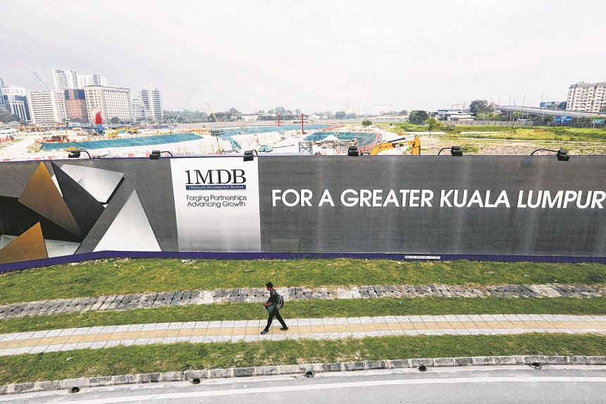 A man walking past a 1MDB billboard at the funds flagship Tun Razak Exchange development in Kuala Lumpur on March 1, 2015.