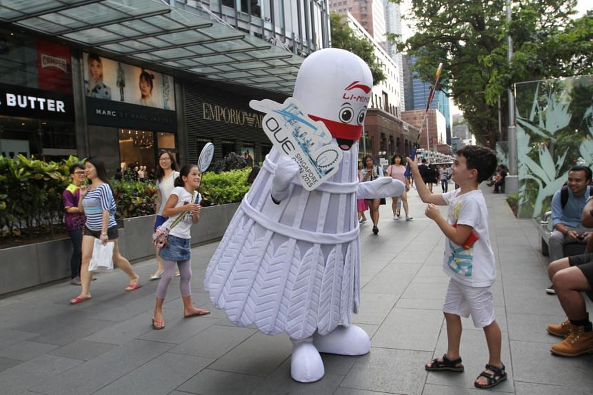 Shuttlecock Man interacting with kids along Orchard Road, as part of the promotion of the OUE Singapore Open.