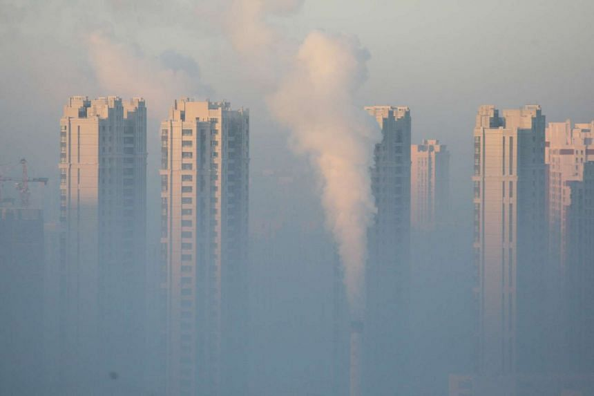 A chimney seen in front of residential buildings during a polluted day in Harbin, Heilongjiang Province.
