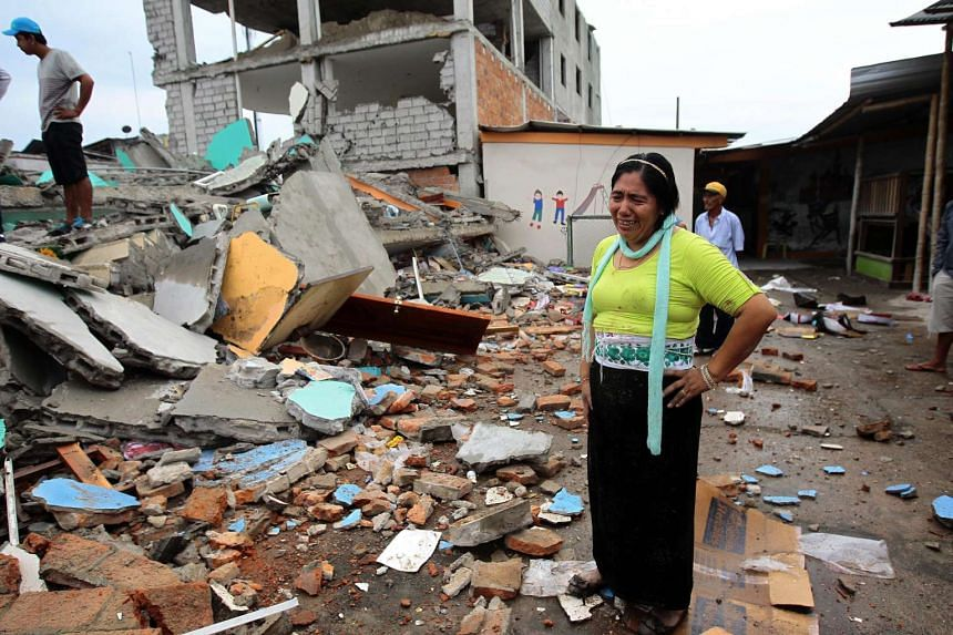 A woman cries in the middle of the debris of a collapsed building in the town of Pedernales, Ecuador on Sunday, after a devastating earthquake.