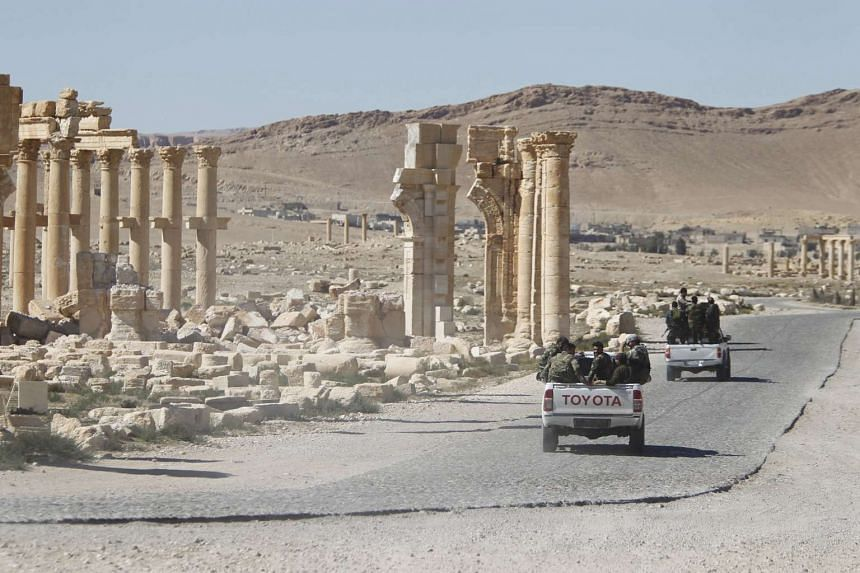 Syrian army soldiers drive past the damaged Arch of Triumph in Palmyra, in Homs Governorate, Syria, on April 1, 2016.