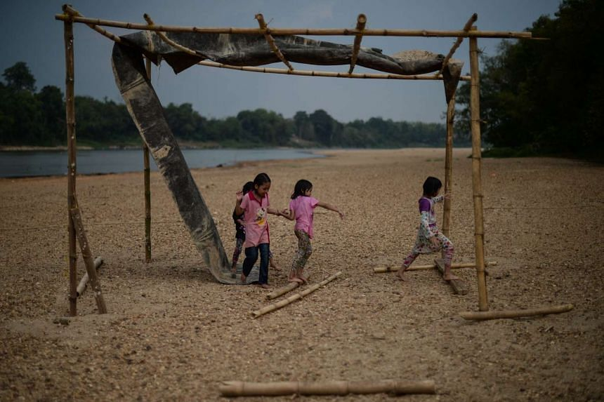 Children play along the dry banks of the Pahang river due to the ongoing heatwave, on April 11, 2016.