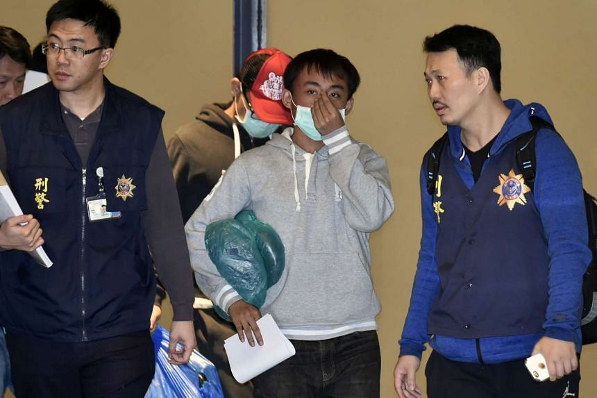 Two masked alleged fraud suspects are escorted by policemen as they arrive at Taoyuan Airport, on April 15, 2016.