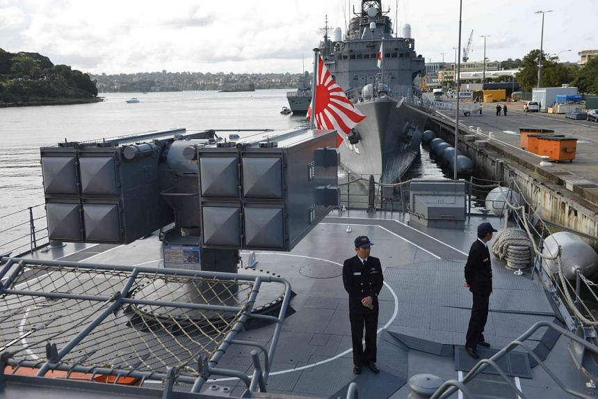 Japanese sailors on the deck of the Japanese Asagiri-class destroyer, JDS Umigiri, docked in Sydney's Naval base, on April 19, 2016.