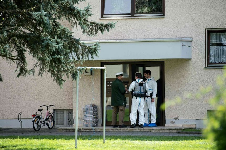 Forensic officers stand at the entrance to the apartment building where the woman was held, in Rosenheim, Germany, on April 19, 2016.
