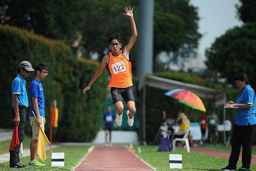 Singapore Sports School's Arfan Azhar (left) won gold in the B Division triple jump, after Hwa Chong Institution's Ernest Ong registered a foul jump.