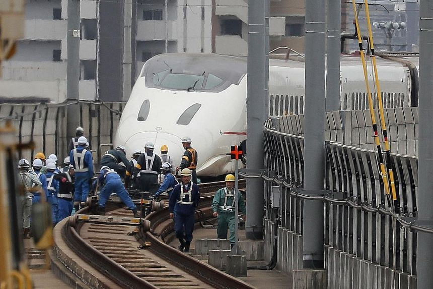 Railway workers yesterday attending to a Kyushu shinkansen (bullet train) after it became derailed during the quake in Kumamoto. At least 42 people are known to have died in the tremors.