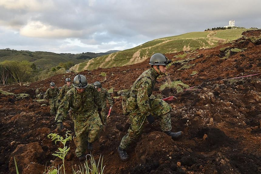 Ground Self-Defence Force troops searching for survivors at a landslide site in Minamiaso. Nine people are still missing, feared buried in collapsed houses.