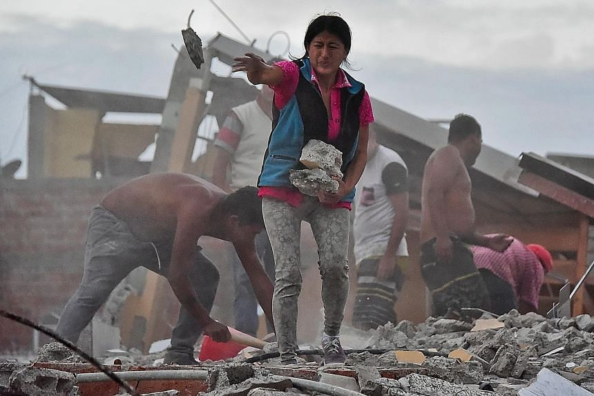 A survivor removing rubble during a search for her husband in a collapsed building in Ecuador's coastal city of Manta on Sunday.