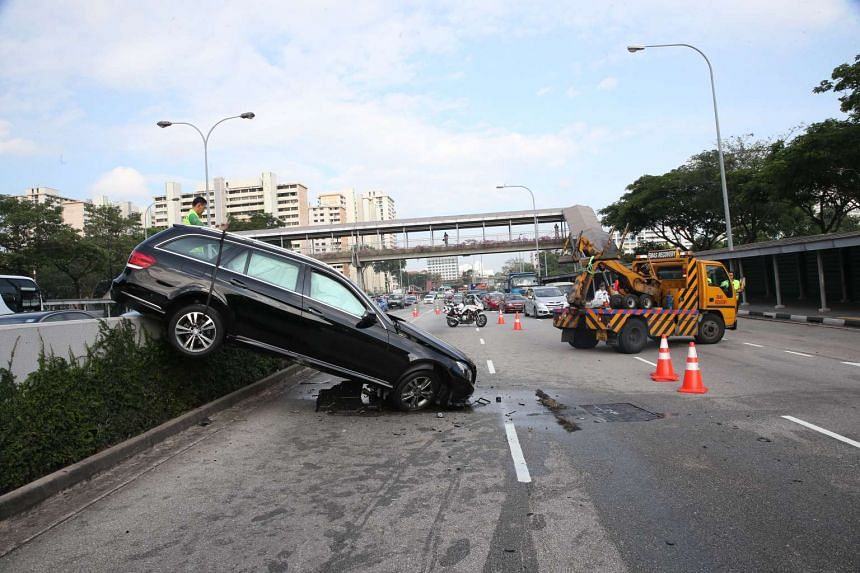 A black station wagon was seen with its rear end atop the centre divider which separated traffic from the Braddell Underpass.