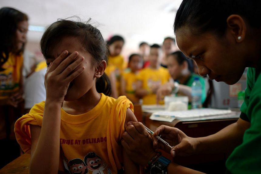 An elementary student grimacing as a nurse administers an anti-dengue vaccine at Parang Elementary School in Marikina, west of Manila on April 4, 2016.