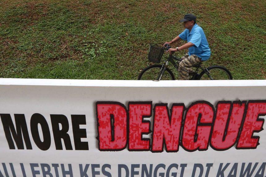 A man cycles past a dengue alert poster along Serangoon North Avenue 1.