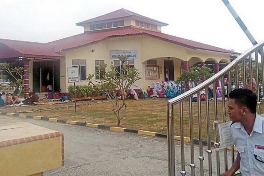 A security guard closing the gate as SMK Kemumin students gather at the school surau to recite religious verses after the school was afflicted with mass hysteria.