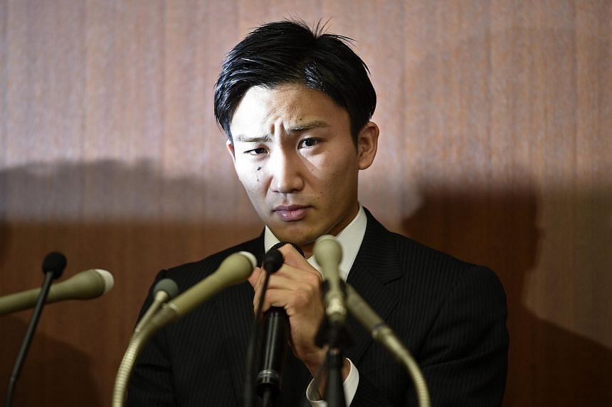 Japanese badminton player Kento Momota reacts during a press conference that was held to apologise after he admitted to gambling at an illegal casino, in Tokyo.