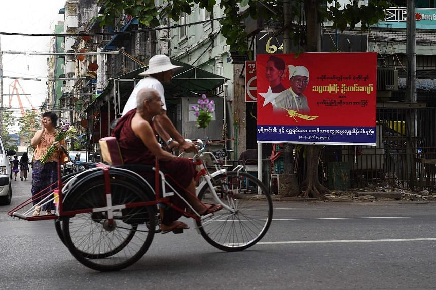 A monk riding on a trishaw commutes past a commercial billboard with portraits of Myanmar's Aung San Suu Kyi and President Htin Kyaw in Yangon, on April 18, 2016.