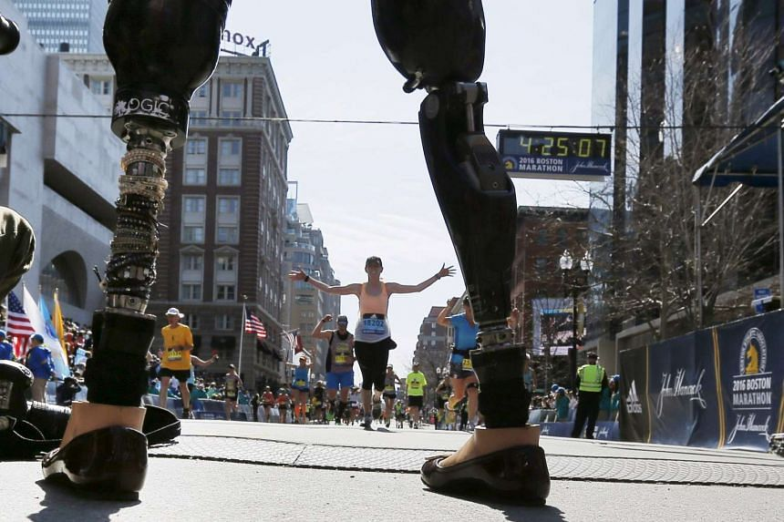 Celeste Corcoran, who lost both her legs in the Boston Marathon bombings, greets runners at they finish the 120th running of the Boston Marathon on Monday (April 18).