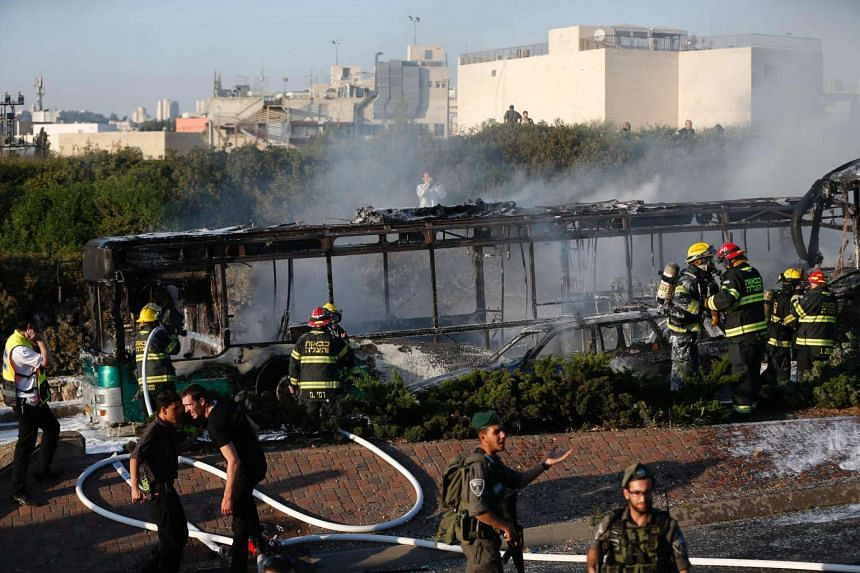 Israeli security forces stand guard as firemen extinguish a burning bus following an attack in Jerusalem on Monday (April 18).