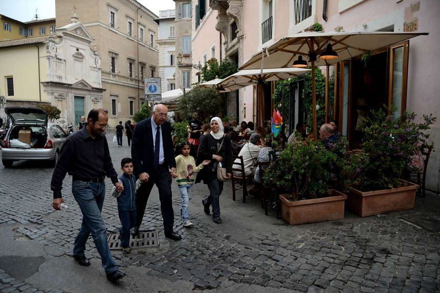 A family of Syrian refugees, part of the Pope's 12 Syrian asylum seekers, walk with a member of the St. Egidio Roman Catholic Charity (centre), on Monday (April 18) in a street of Rome.