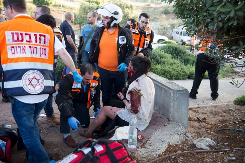 Israeli emergency workers help an injured woman at the scene where an explosion tore through a bus in Jerusalem on Monday (April 18).