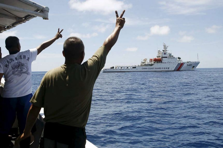 Filipino soldiers gesture at a Chinese Coast Guard vessel on the disputed Second Thomas Shoal, part of the Spratly Islands, in the South China Sea.