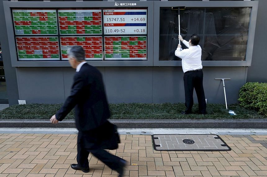 A man (right) cleans electronic boards showing Japan's Nikkei average, outside a brokerage in Tokyo.