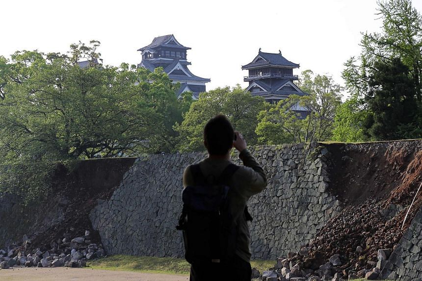 A man takes a picture of a collapsed stone wall at Kumamoto Castle on April 15, 2016.