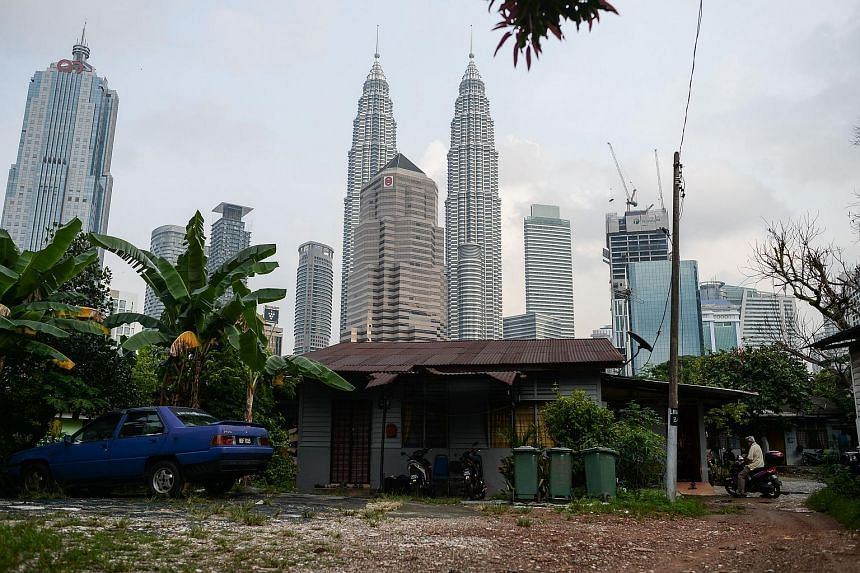 A man (right) riding a motorcycle near his wooden home as Malaysia's iconic Petronas Twin Towers loom in the background in Kampung Baru.