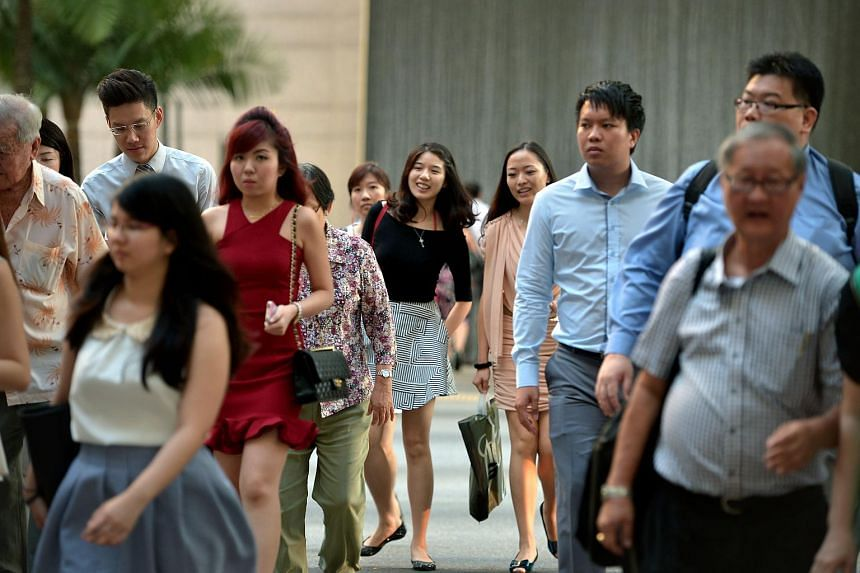 Office workers walking along Shenton Way, on April 14, 2015.