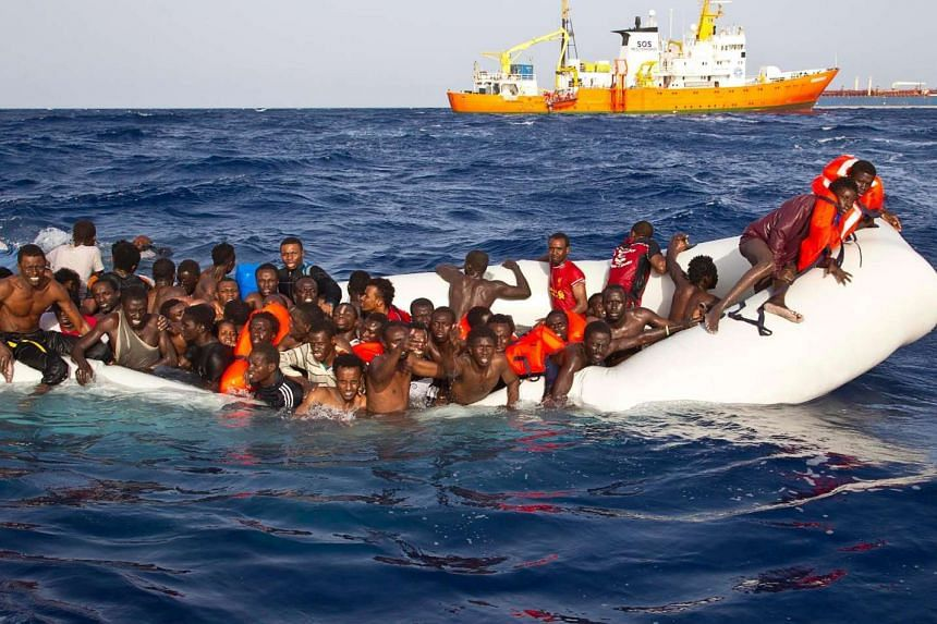 Migrants on a sinking inflatable boat before being rescued by the Aquarius ship of the humanitarian group SOS Mediterranee on April 18, 2016.