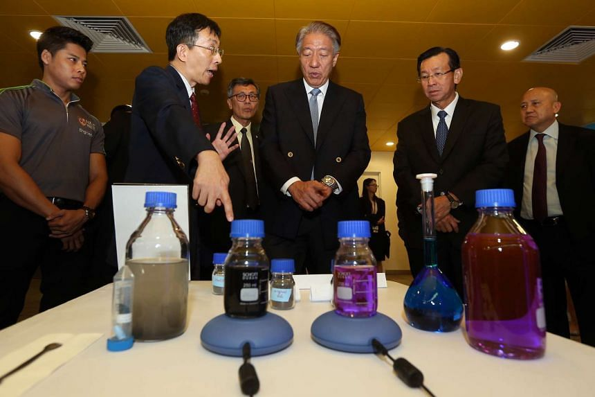 Professor Wang Chi Hwa (second from left) talks to Deputy Prime Minister Teo Chee Hean (centre) during a tour of the exhibition at the launch of Sembcorp-NUS Corporate Laboratory.