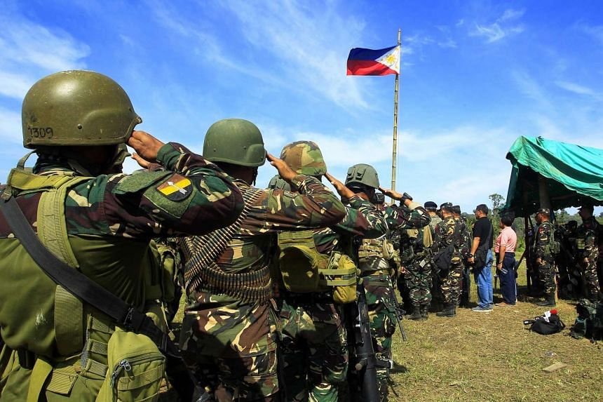 Philippine soldiers saluting at the end of their operation against Islamic militants in Mindanao on March 1, 2016.