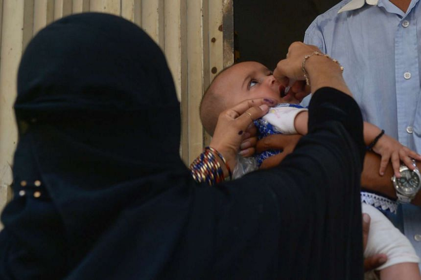A Pakistani health worker administers polio drops to a child during a polio vaccination campaign in Karachi on March 15, 2016.