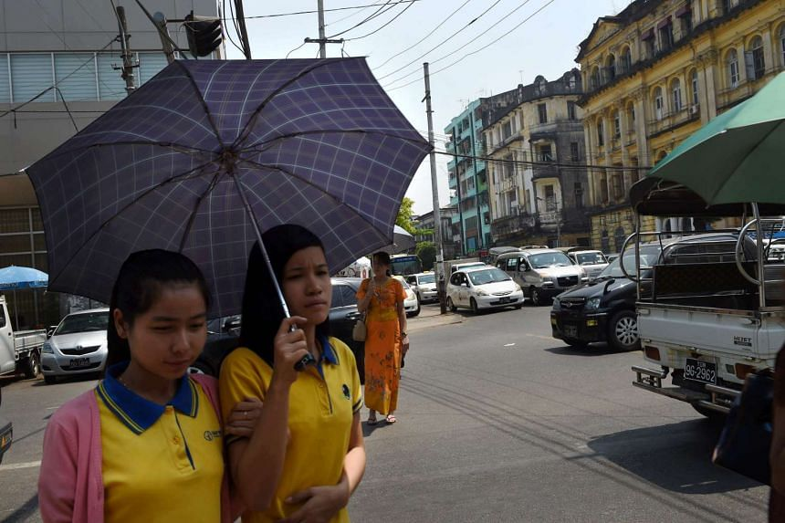 Myanmar women use an umbrella in Yangon on March 19, 2016,