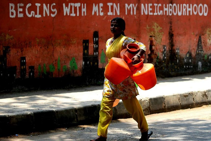 A woman carries plastic pots during a heat wave in Bangalore, Karnataka, India on April 16, 2016.