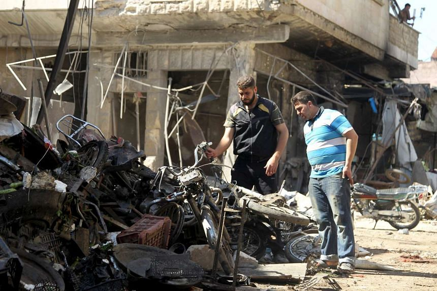 Men inspect damaged motorcycles after an airstrike on a market in the town of Maarat al-Numan in the insurgent stronghold of Idlib province, Syria on April 19, 2016.
