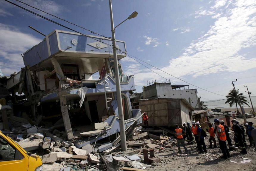 Rescue team members and policemen search for victims at a collapsed hotel after an earthquake struck off the Pacific coast in Pedernales, Ecuador on April 19, 2016.
