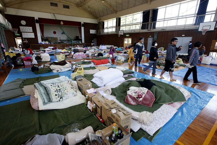 Japanese earthquake victims walk within an earthquake evacuation center in Minamiaso, Kumamoto Prefecture on April 20, 2016.